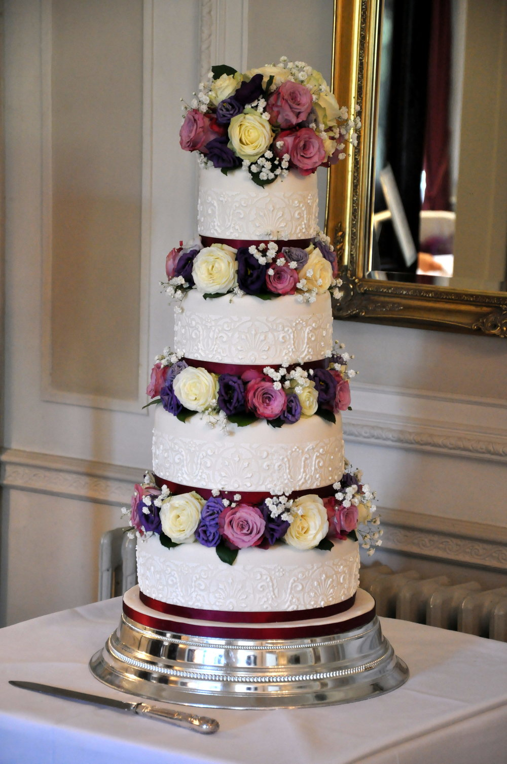 - A stylish and classic four tier wedding cake, with fine stenciling and fresh flowers for decoration.