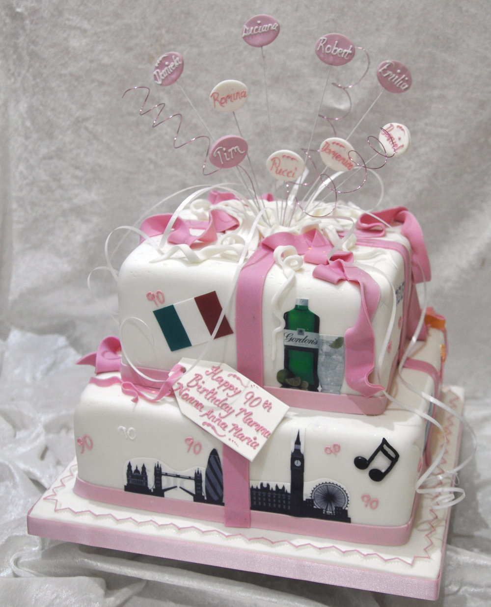 Parcel explosion - A very personal parcel explosion cake made for an elegant Italian lady on her landmark birthday.  The names of her family hand piped on decal plaques, wires, pictures and hand made sugar pieces, with our signature explosion making a super cake suitable for a fun party.