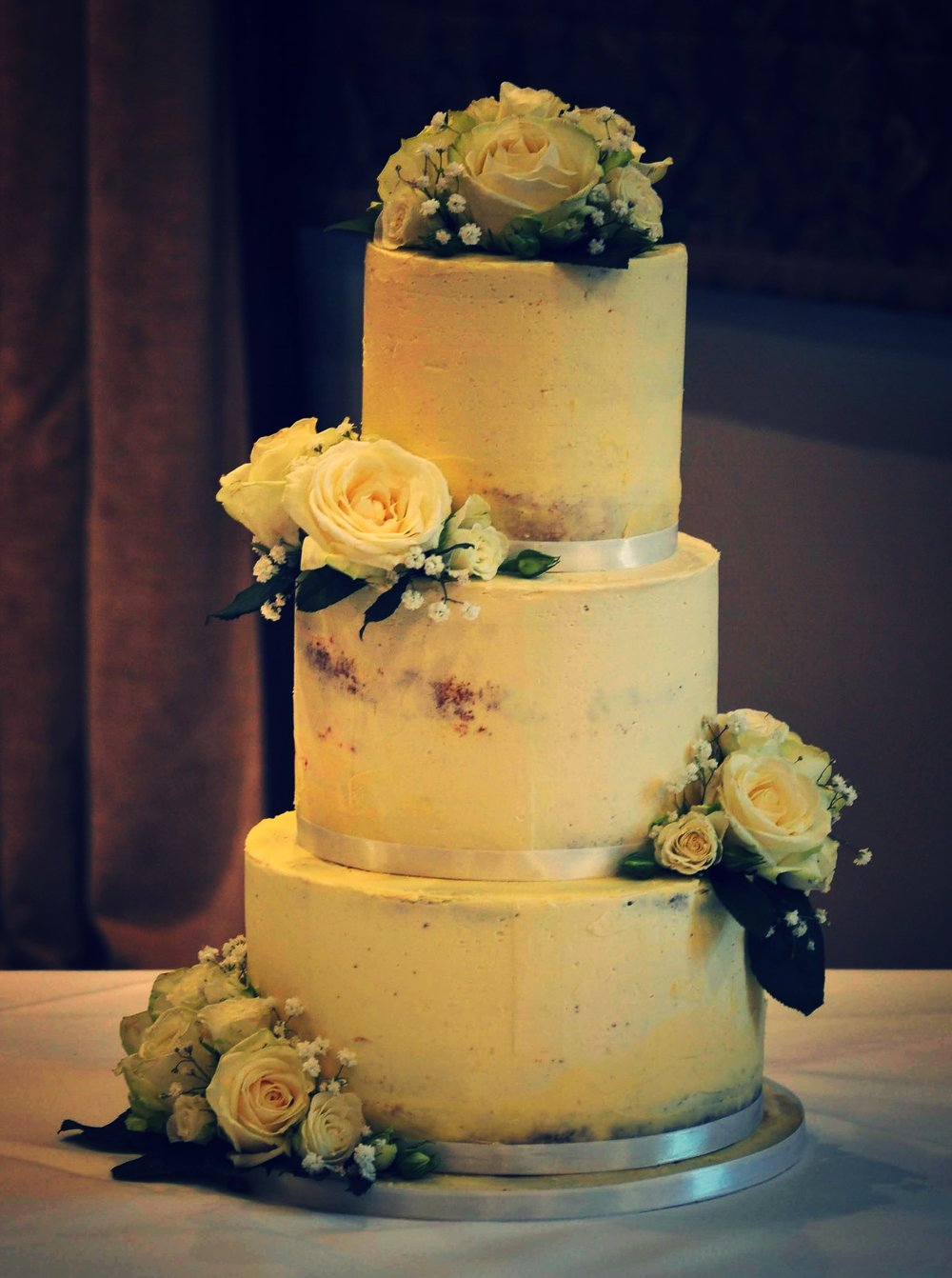 Semi naked wedding cake - Here is a fabulously delicious gluten free wedding cake. The tiers were white chocolate and Baileys cream, vanilla with fresh strawberry jam and zesty lemon on the top. Scumptious!