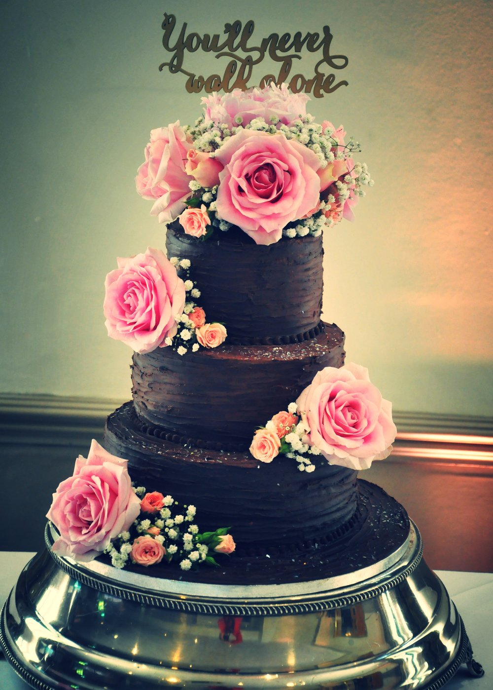 Chocolate ganache  - Three tier chocolate wedding cake with ganache and dark chocolate finish.  The cake is made from 3 layers of chocolate orange, chocolate coffee and bitter dark chocolate.  Decorated with fresh flowers.