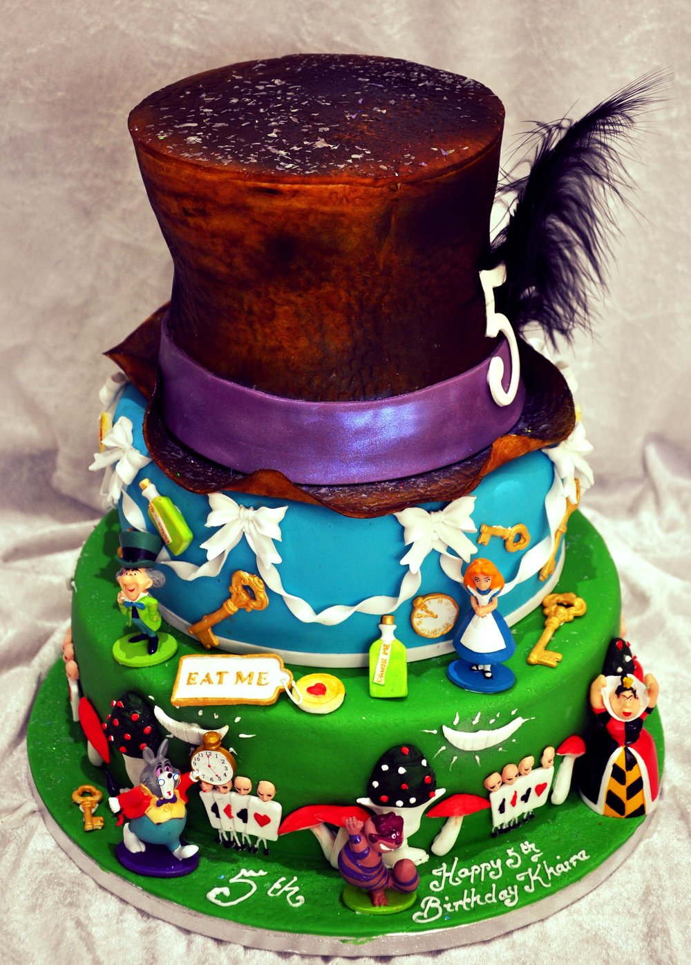 Alice in Wonderland - Three tier Alice In Wonderland cake, with a mixture of hand made sugar and plastic figures. finished with the Mad Hatter's hat and personal message.