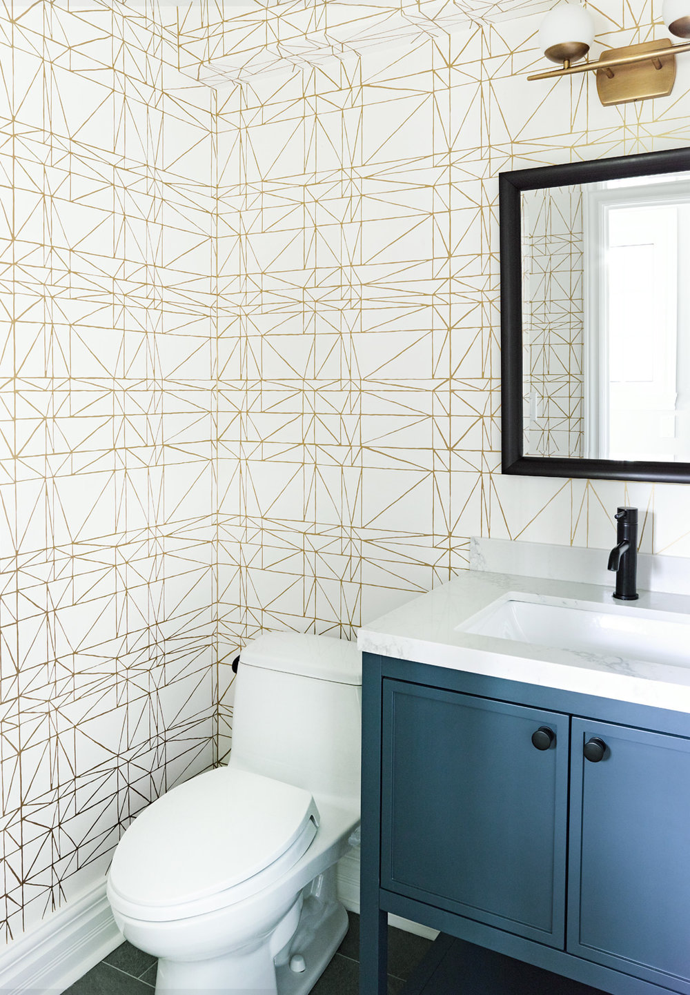 Blue Vanity in powder room with schumacher wallpaper