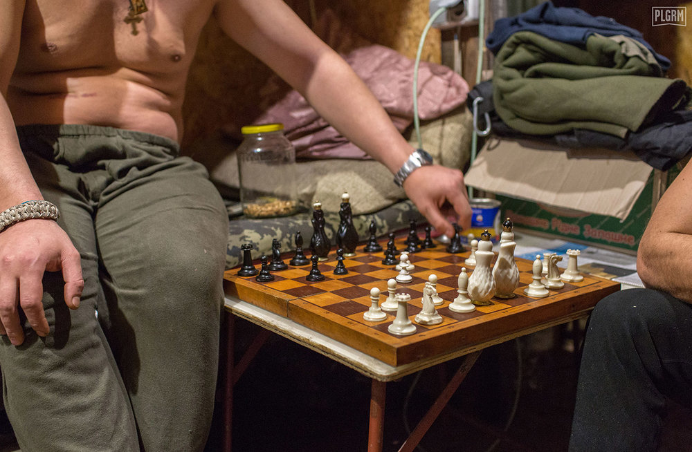 Chess is a common way to pass time during the nights in Donetsk. Two Ukrainian soldiers play against each other after beating me three times in a row.