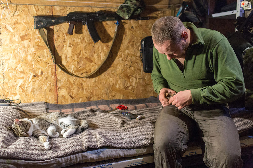 Mice are a common problem in Ukrainian positions. This Ukrainian soldier rigs a homemade mouse trap, while a cat sleeps nearby.
