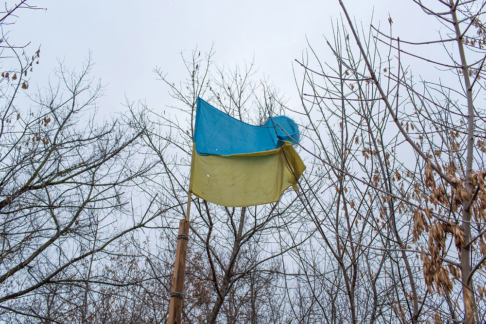 This Ukrainian flag is riddled with shrapnel damage from its time flying in Pisky.