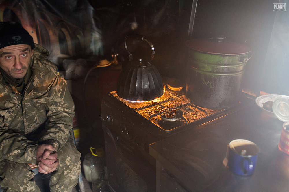 A Ukrainian soldier retreats from the cold wind of morning inside of a small kitchen and food area.