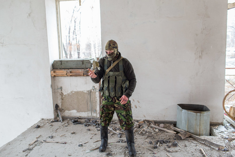 A Ukrainian soldier playfully tosses a grenade during a visit to old 93rd Brigade positions.