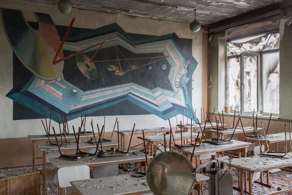 A mural on a wall in a classroom in Pisky's school. Stools and chairs still remain on tables following the the displacement of Pisky's civilian residents.