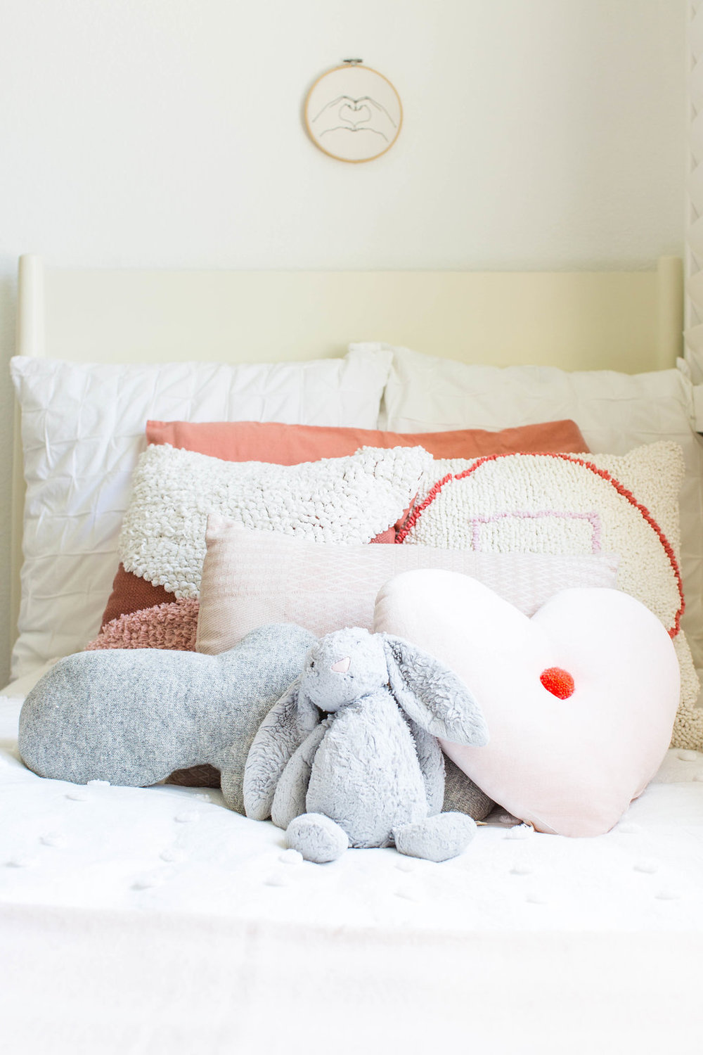 bed  |  white pom duvet  |  blush throw  | pink accent pillows & embroidery art (discontinued from target) |  cloud pillow (similar) |  heart pom pillow  |  bunny