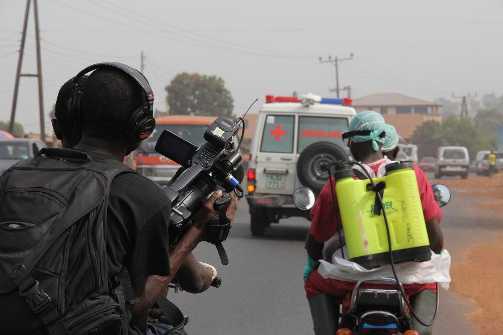 'Survivors' co-director Arthur Pratt holding camera on the back of an Okada.