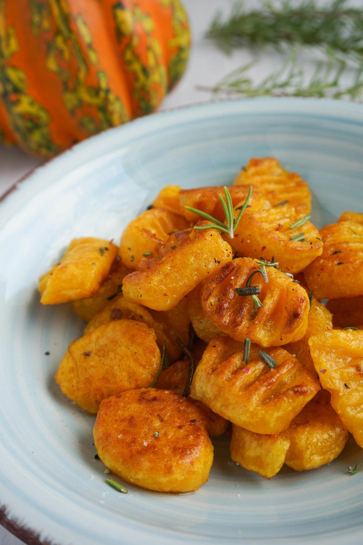 Du brauchst: - 2 Tassen gegarten Kürbis2-3 Tassen Kartoffelmehl/stärkeÖl zum AnbratenGewürze & frische Kräuter nach Wahl (z.B. Salz, Pfeffer & Rosmarin)