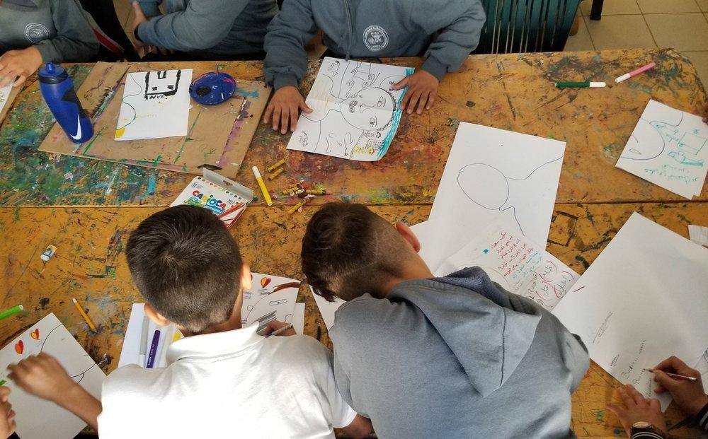 Two boys draw their self portraits. Diyar Academy for Children & Youth, Bethlehem