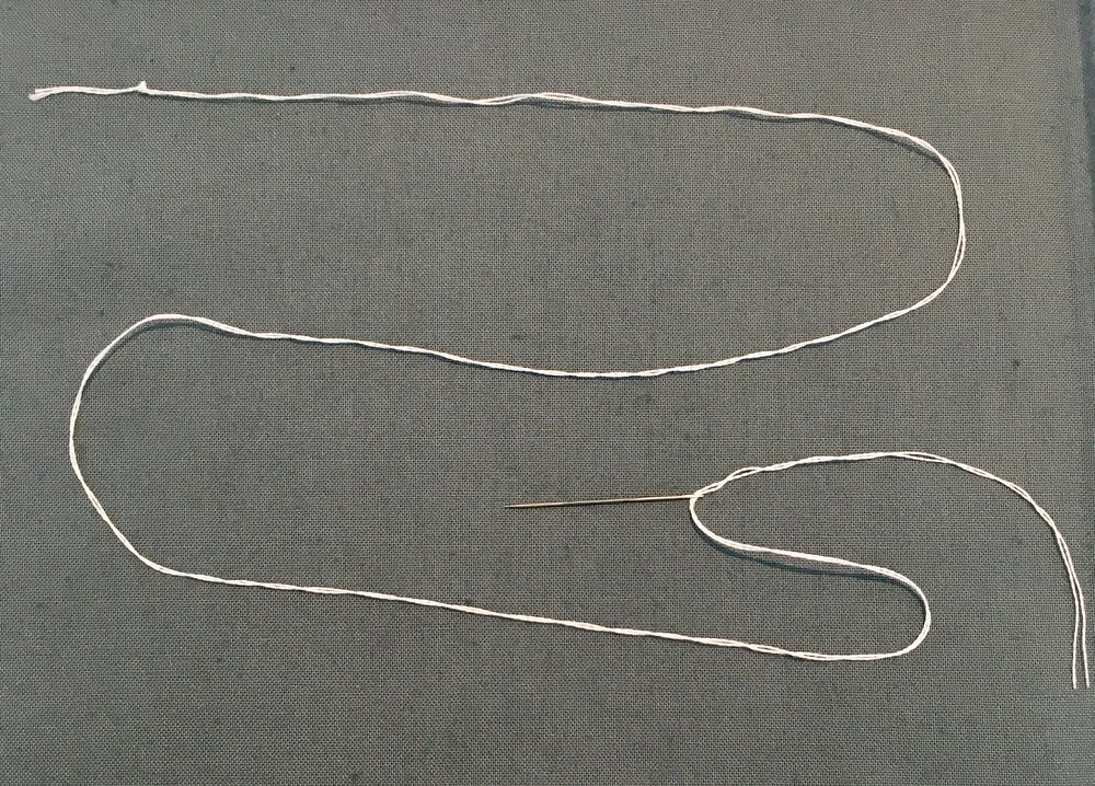 Leave some excess floss near the head or eye of the needle, and at the very end of the length of the floss, tie a knot to act as an anchor for your first stitch. Ideal floss length is up to you, but about arm's length is usually good. Too short, and you have a lot of stopping and starting with new strands. Too long, and you get tangles and knots while you're working.