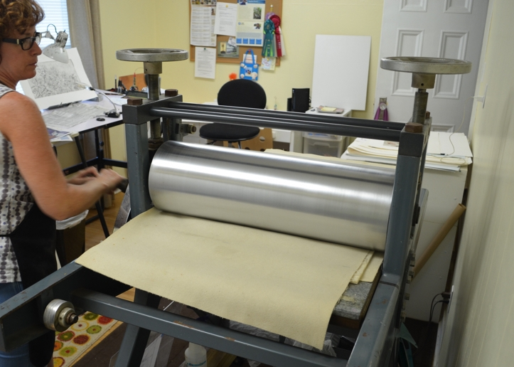 - The crank is turned to roll the press bed under the drum.