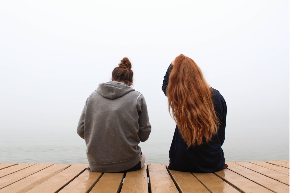 Two women sitting on a dock with their backs facing the camera.