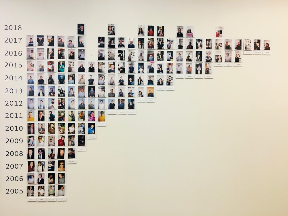 Call-Em-All's picture wall. On your first day, plus on every work anniversary, you get a picture taken and added to the wall.