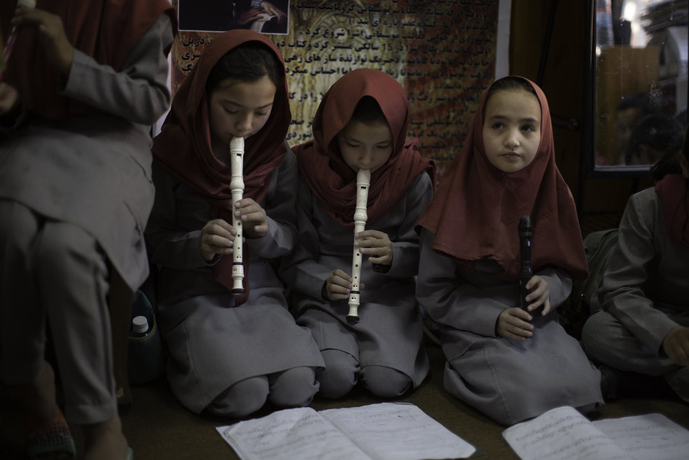 Afghan girls practice their recorders with an instructor.