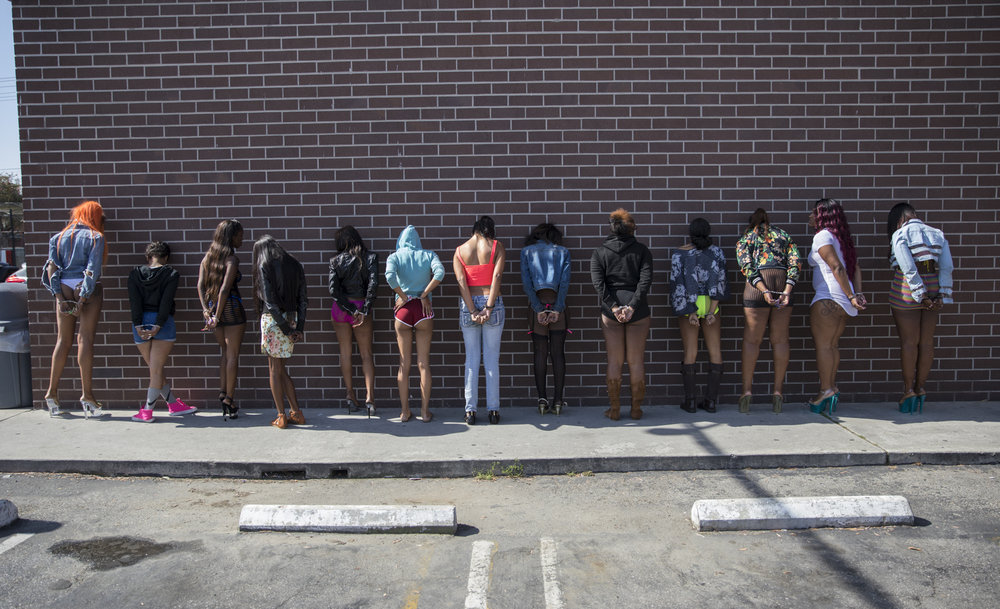 May 18, 2017: Officers of the Los Angeles Police Department's vice squad prepare thirteen women for transportation after being arrested for prostitution in the southeast area of Los Angeles, California. The women were arrested for soliciting undercover police officers for the purpose of prostitution. All thirteen women were arrested in a span of 30 minutes starting at 5:35am along Figueroa Street, a renowned thoroughfare for prostitution
