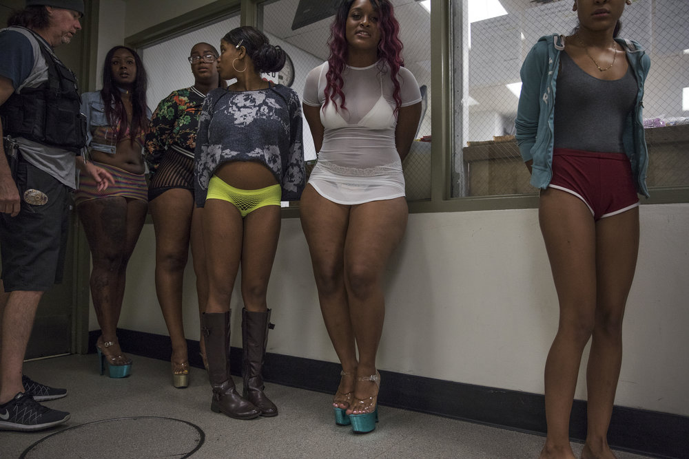 May 18, 2017: Sgt Scott Carty, left, an officer with the Los Angeles Police Department's vice squad, escorts 13 women arrested earlier in the day to a holding cell at the South East division's police headquarters in Los Angeles, California. The women were arrested for soliciting undercover police officers for the purpose of prostitution, a misdemeanor charge.