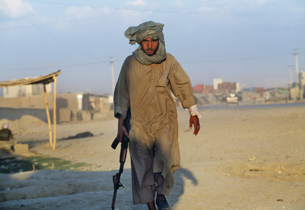 May 1997: A Taliban soldier walks away from where his comrade was shot down in Mazar-I-Sharif. A recent power sharing agreement with Uzbek and Hazara militias and the Taliban broke down after 36-hours. The Taliban were unaware that the Uzbeks and Hazaras had drawn them into a trap.