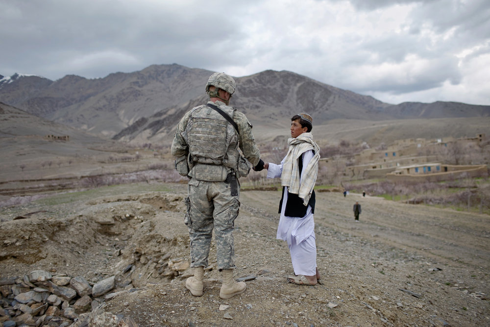 A U.S. soldier shakes the hand of an Afghan youth outside the town of Jalrez in Wardak province. The hilltop overlooking apple and almond orchards had fighting trenches, left of the soldier, built by Afghan mujahideen 25 years ago in their fight against Soviet forces.