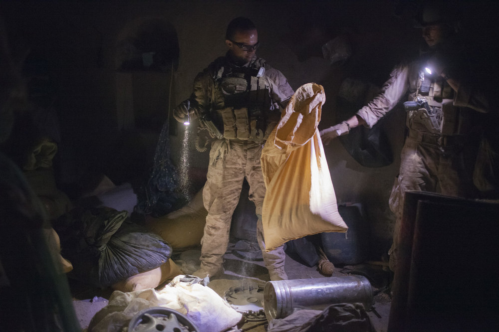 August 2009: U.S. Marines investigate possible bomb making ingredients at a farmer's home in Khan Neshin, Helmand province. The team concluded the fertilizer was for agricultural use.