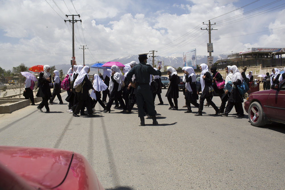 May 2013: A policeman stops traffic as schoolgirls cross a main roadway in western Kabul. Female literacy rate in Kabul is 37%, the highest in the country.