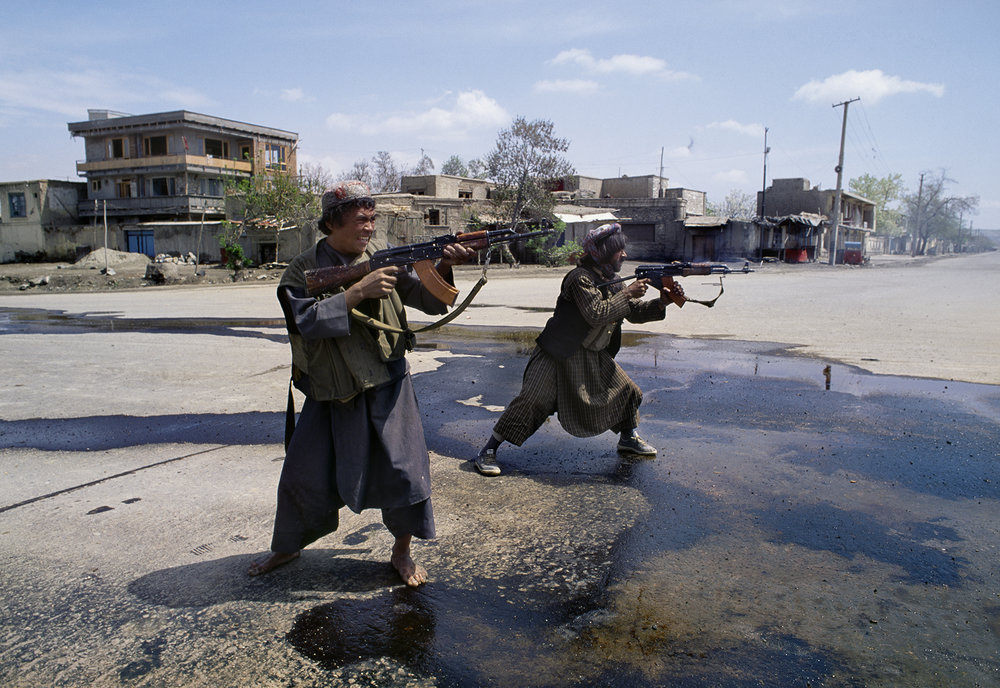 April 1992: Afghan Uzbek fighters under the control of Abdul Rashid Dostum fire on Hizb-i-Islami forces of Gulbuddin Hekmatyar in the southwest part of Kabul, during the mujahideen seizure of the city. The takeover of Kabul became a battle between mujahideen groups, divided along ethnic and geographic regions, attempting to seize control of government ministries.