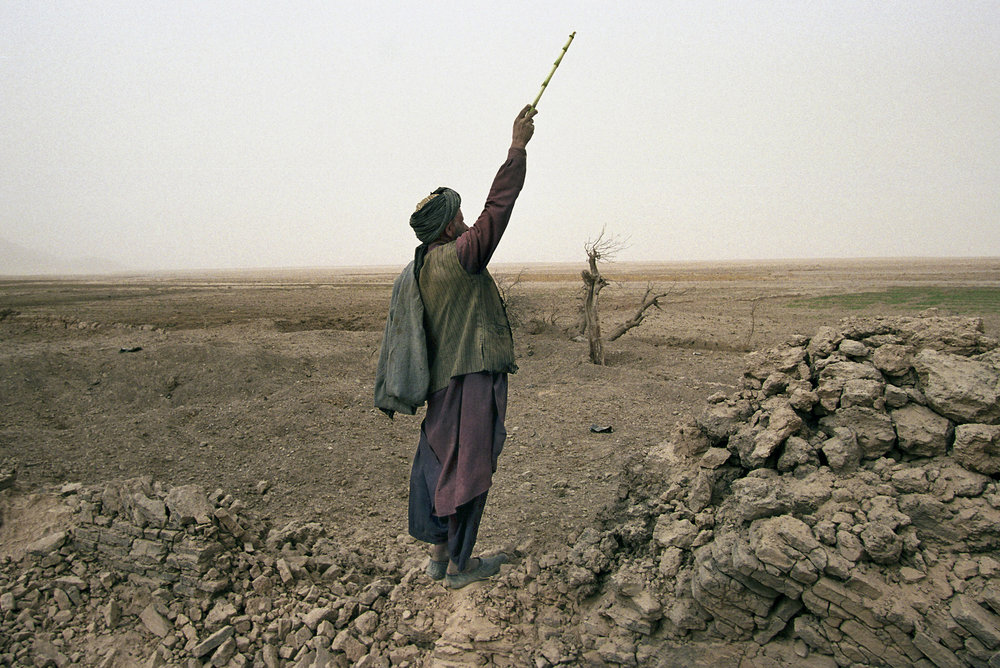 November 2001: An Afghan shepherd in Chowkar Karez, Kandahar province, shouts to his children to lead their flock of goats over to him. He stands by a wall bombed by U.S. and French aircraft. The death toll was nearly 25 civilians, although local residents claim Al Qaeda or Taliban were not present during the attacks. The U.S. Army called the town a military target occupied by one of the groups.