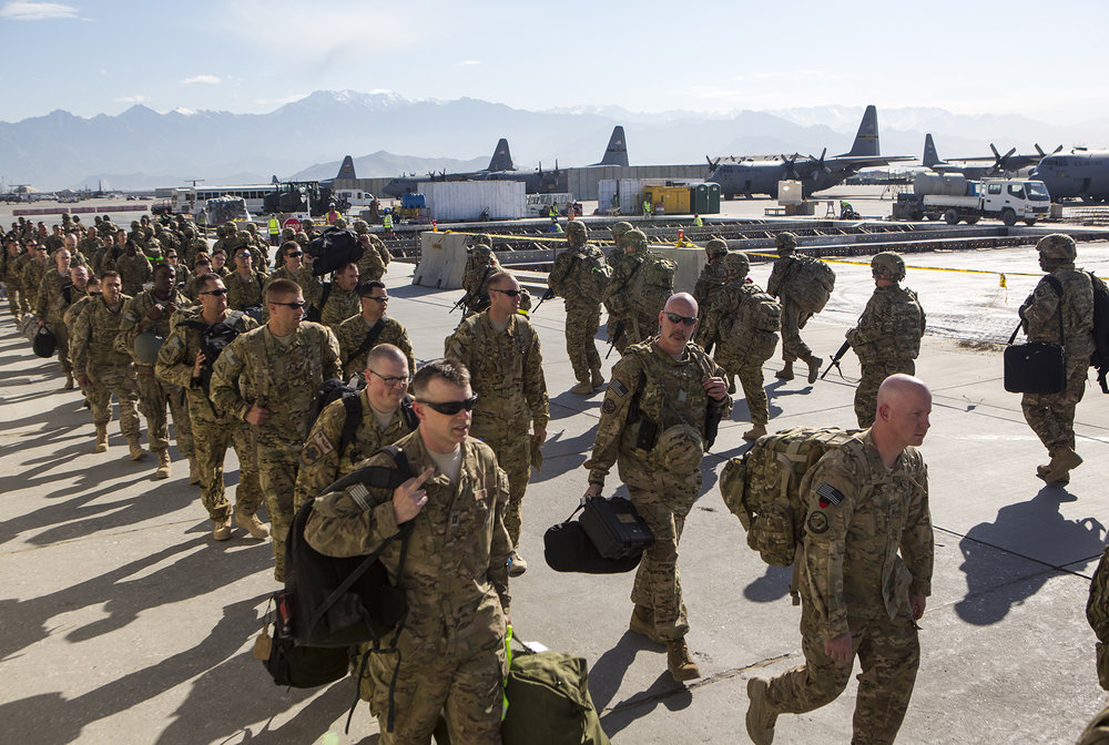 May 2013: A contingent of American troops concludes their tour in Afghanistan and prepare to fly home from Bagram Air Base. Others arrive, wearing their helmets. With the Western military presence winding down in the months before the December 2014 withdrawal deadline, the United States continues to provide the largest contributions of men, women, and assistance.