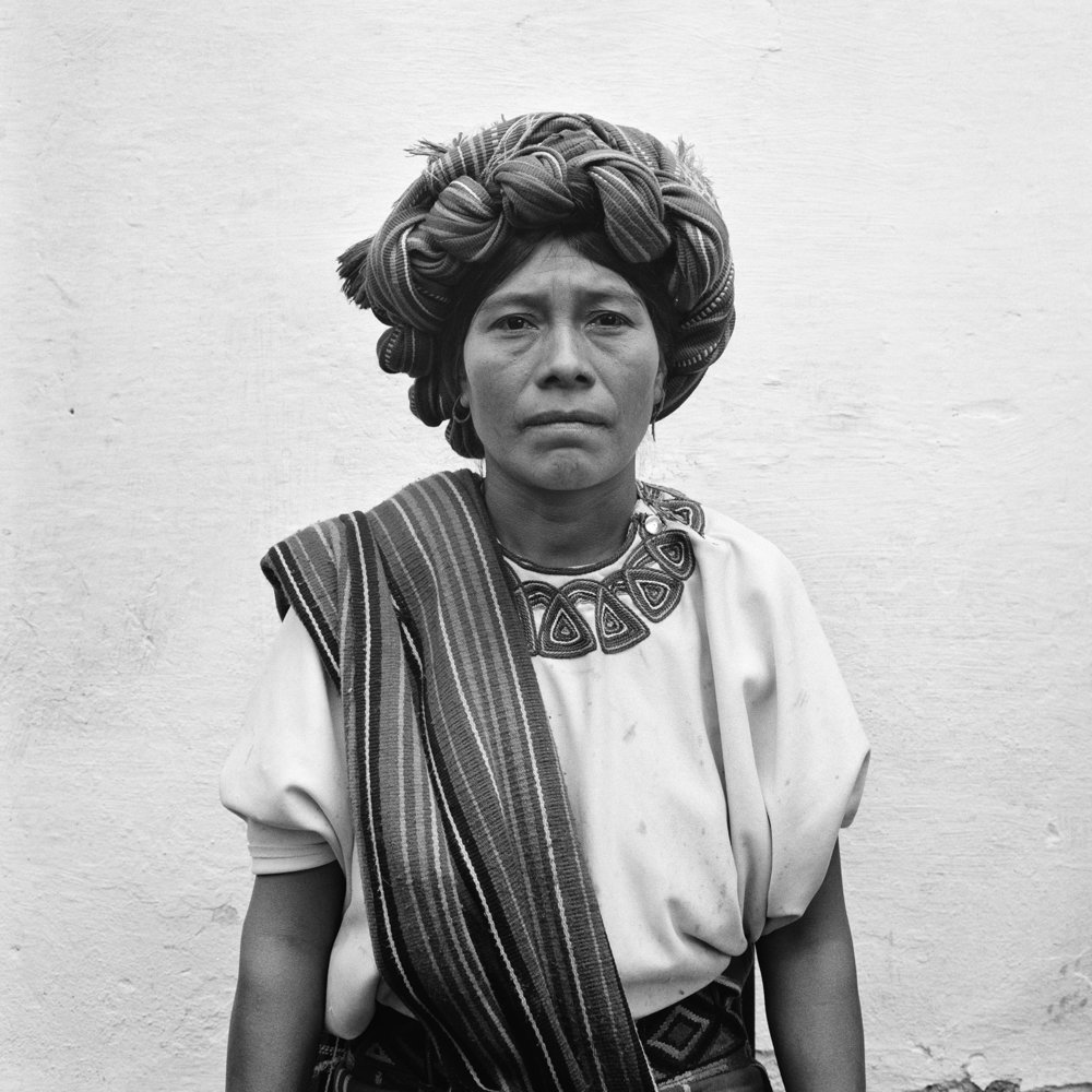 An Ixil Maya woman wearing a traditional head dress stands for a picture in Nebaj, Guatemala, January 1, 1984.