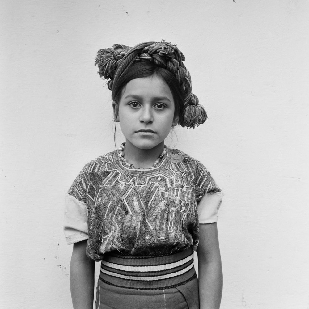 A young Ixil Maya girl, Clara Luz Brito Raymundo, 9 years, wearing a traditional head dress stands for a picture in Nebaj, Guatemala, January 1, 1984.