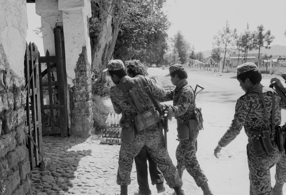 Army soldiers direct a suspected leftist guerrilla into a building for interrogation in the military compound in Santa Cruz del Quiché, Guatemala, January 1, 1982.