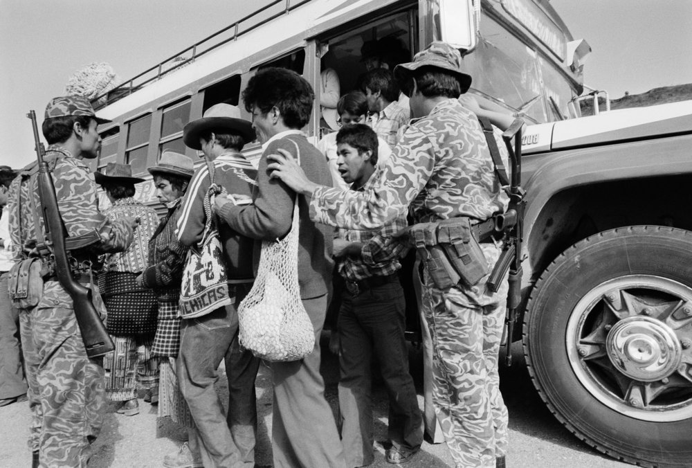 Army soldiers check identity cards of bus passengers along the Pan American Highway to Chichicastenango, Guatemala, March 1, 1982. The Lucas García government and the Guatemalan army had initiated a brutal counterinsurgency program using scorched earth tactics, primarily targeting the Maya population of the highlands and urban centers in an effort to consolidate control over civilians and counteract the influence of insurgency.