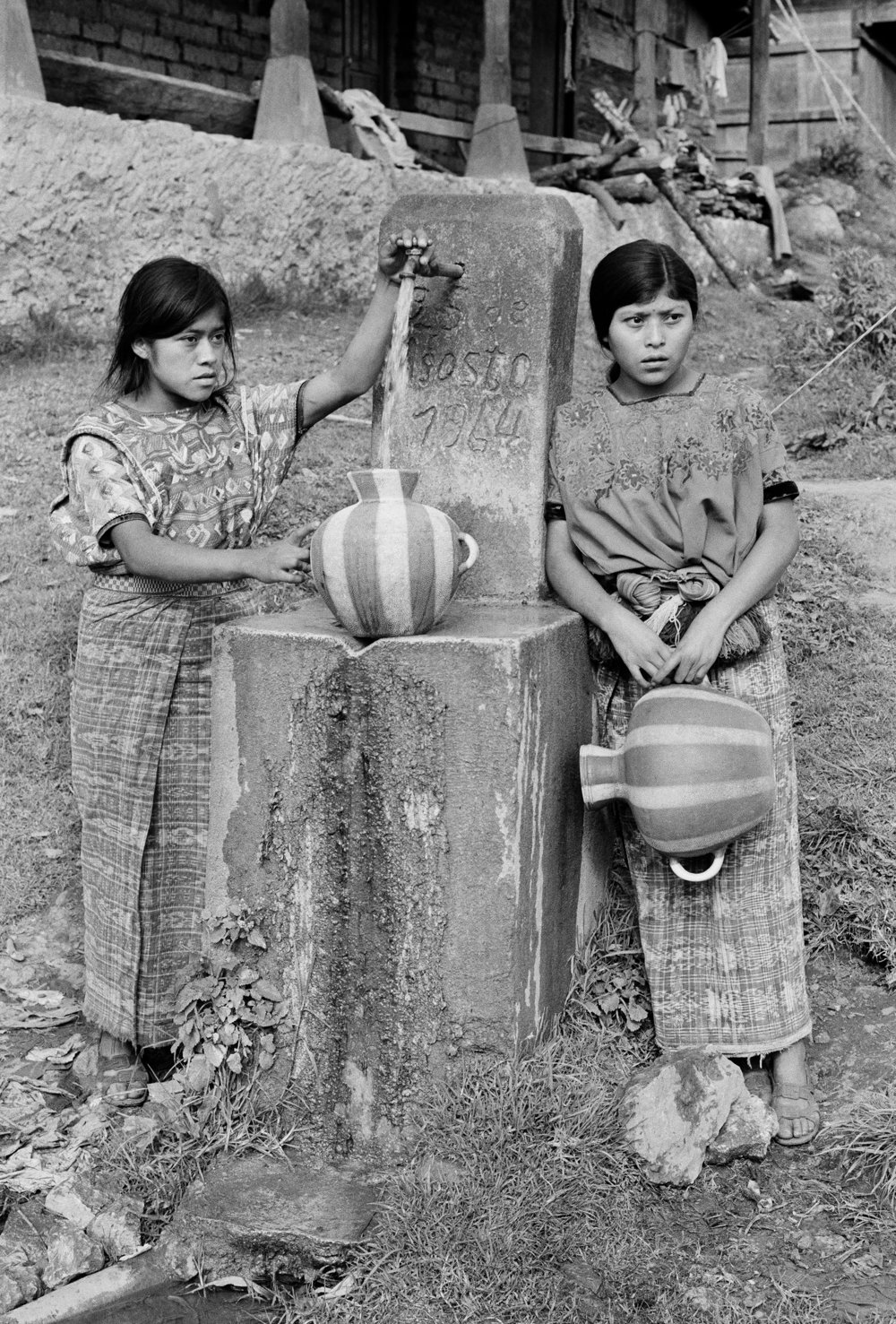 Two young Mayan Indian women retrieve water January 1982 following an early morning gun battle between leftist guerrillas from the Guerrilla Army of the Poor, EGP, and Guatemalan army soldiers stationed in San Juan Cotzal, Guatemala. Over one hundred EGP guerrillas attacked the highland base leaving twelve soldiers dead.
