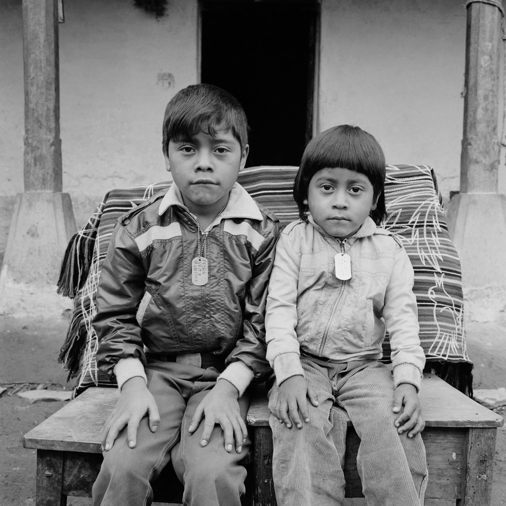 Two Mayan children wearing name tags sit for a picture May 1984 in Nebaj, Guatemala.