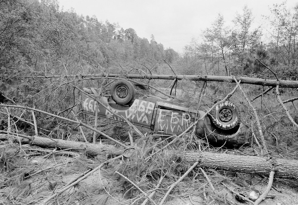 A section of the Pan American Highway was blocked by felled trees and a destroyed car during the ongoing civil war, March 7, 1982 in Los Encuentros, Guatemala. The trees were downed by the Guerrilla Army of the Poor, or EGP, to block the road the day of presidential elections.