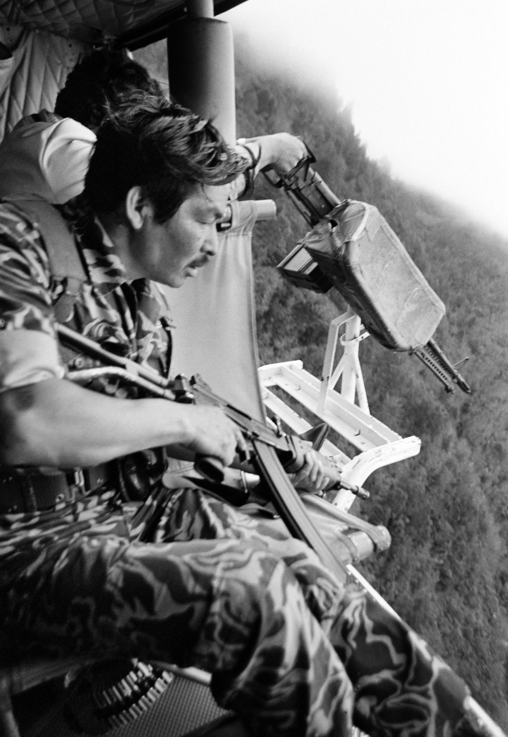 Army soldiers fire on local Maya people from a US-made Bell helicopter co-piloted by Guatemalan army General Benedicto Lucas García outside of Santa Cruz del Quiché, Guatemala, January 1, 1982. Scorched earth was a brutal counterinsurgency tactic employed by the Guatemalan military that holistically targeted the insurgent base through complete destruction of infrastructure and food supply, as well as the persecution of civilians suspected of aiding the guerrilla cause. For his role as army general in the internal armed conflict, Benedicto Lucas García was sentenced on May 23, 2018 to 58 years of prison for crimes against humanity, aggravated sexual violence and enforced disappearance.