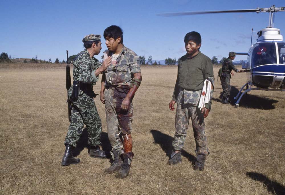 Guatemalan army Colonel Lima Estrada, left, checks on two wounded soldiers brought for medical aid to the army garrison in Santa Cruz del Quiché, Guatemala on January 20, 1982.