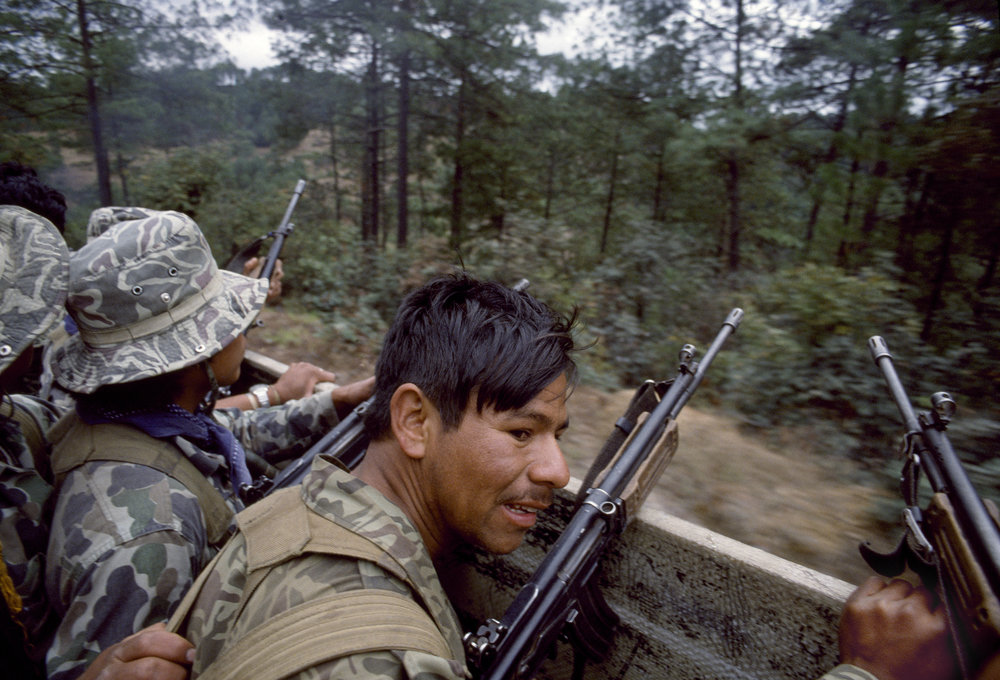 Guatemalan army soldiers travel in a U.S. manufactured troop transport through possible guerrilla ambush terrain outside of Santa Cruz del Quiché on February 1, 1982. The soldiers use Israeli-supplied Galil rifles.