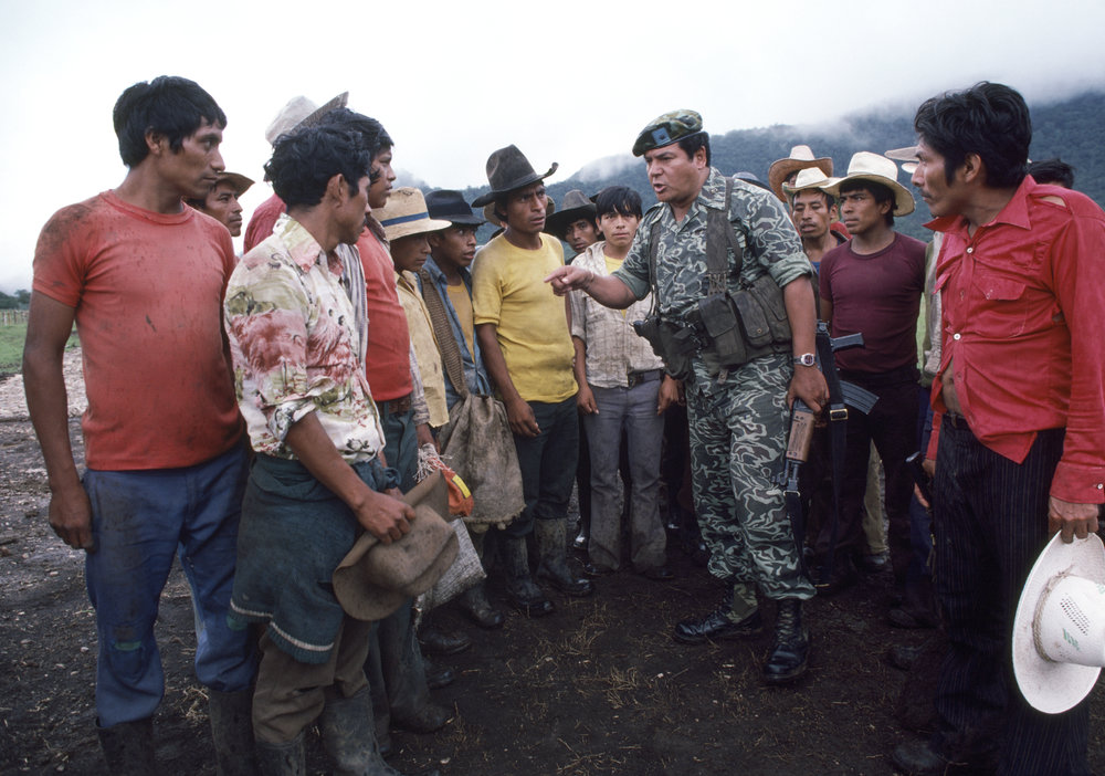 Local male residents listen to a Guatemalan army officer, center, speak about forming civil defense patrols to secure their villages against leftist guerrilla attacks near Huehuetenango, Guatemala on October 1, 1982.