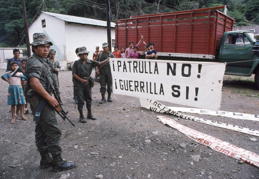 Local residents watch as Guatemalan army soldiers show captured banners made by a leftist guerrilla group, Guerrilla Army of the Poor, EGP, in Huehuetenango, Guatemala October 1, 1982.
