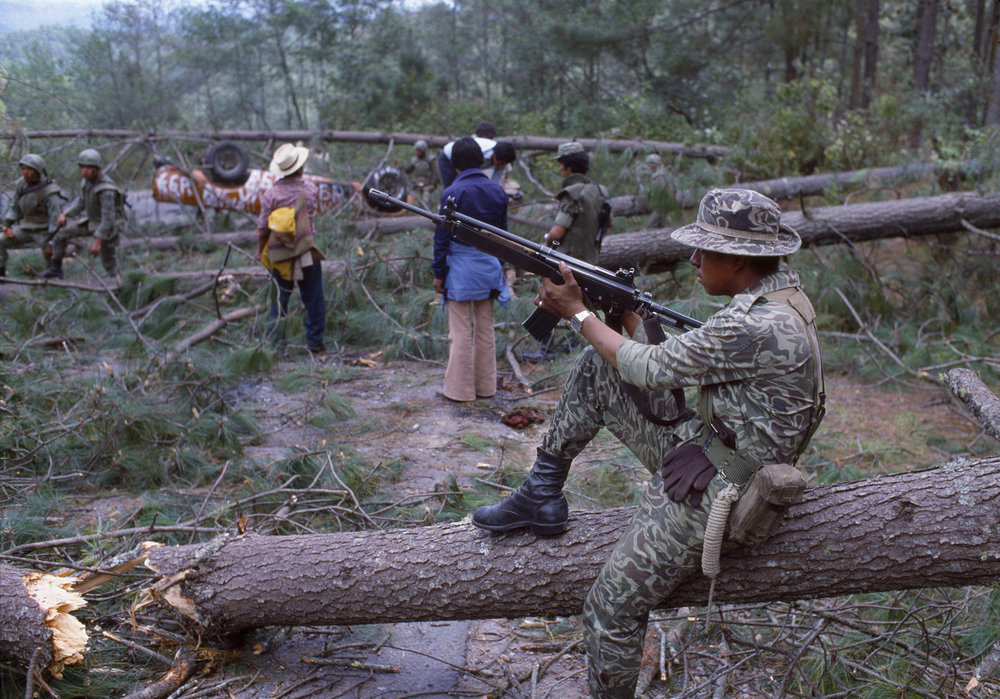 Guatemalan army soldiers and unidentified locals clear a section of the Pan American Highway blocked by felled trees during the ongoing civil war in Los Encuentros, Guatemala March 7, 1982. The trees were cut by the Guerrilla Army of the Poor, EGP, blocking the road the day of presidential elections.