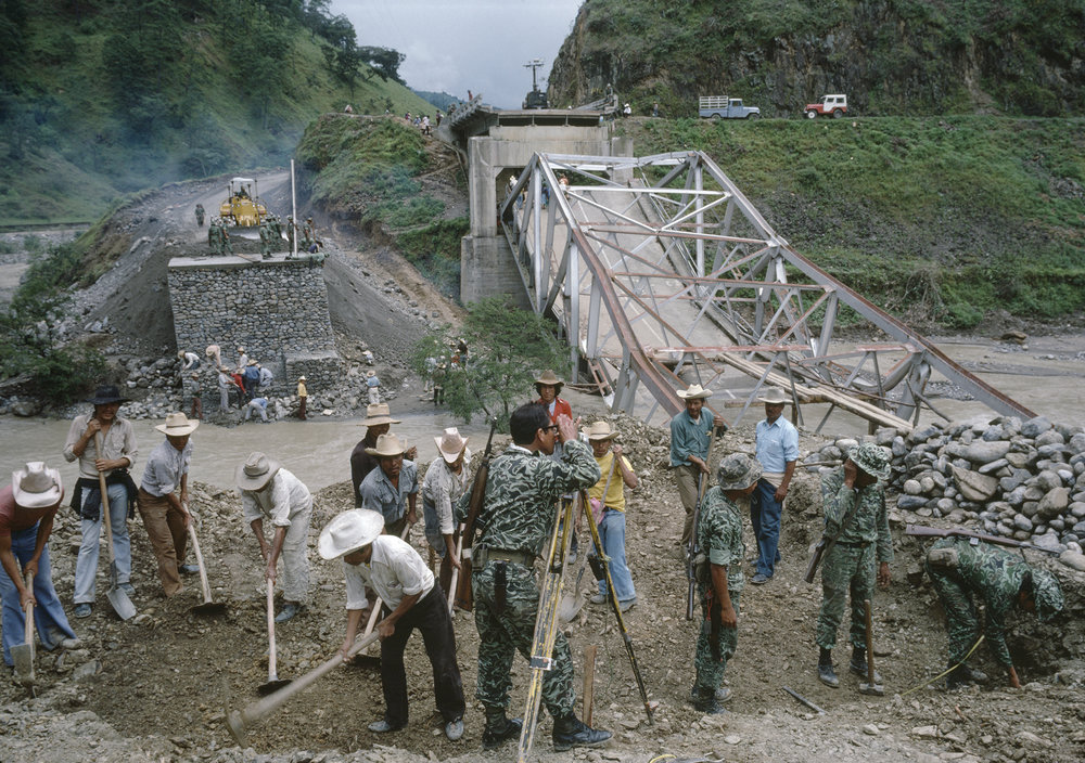 Guatemalan army engineers and local militia units help with replacing a bridge blown up by leftist insurgent groups in rural Huehuetenango, Guatemala on October 1, 1982.