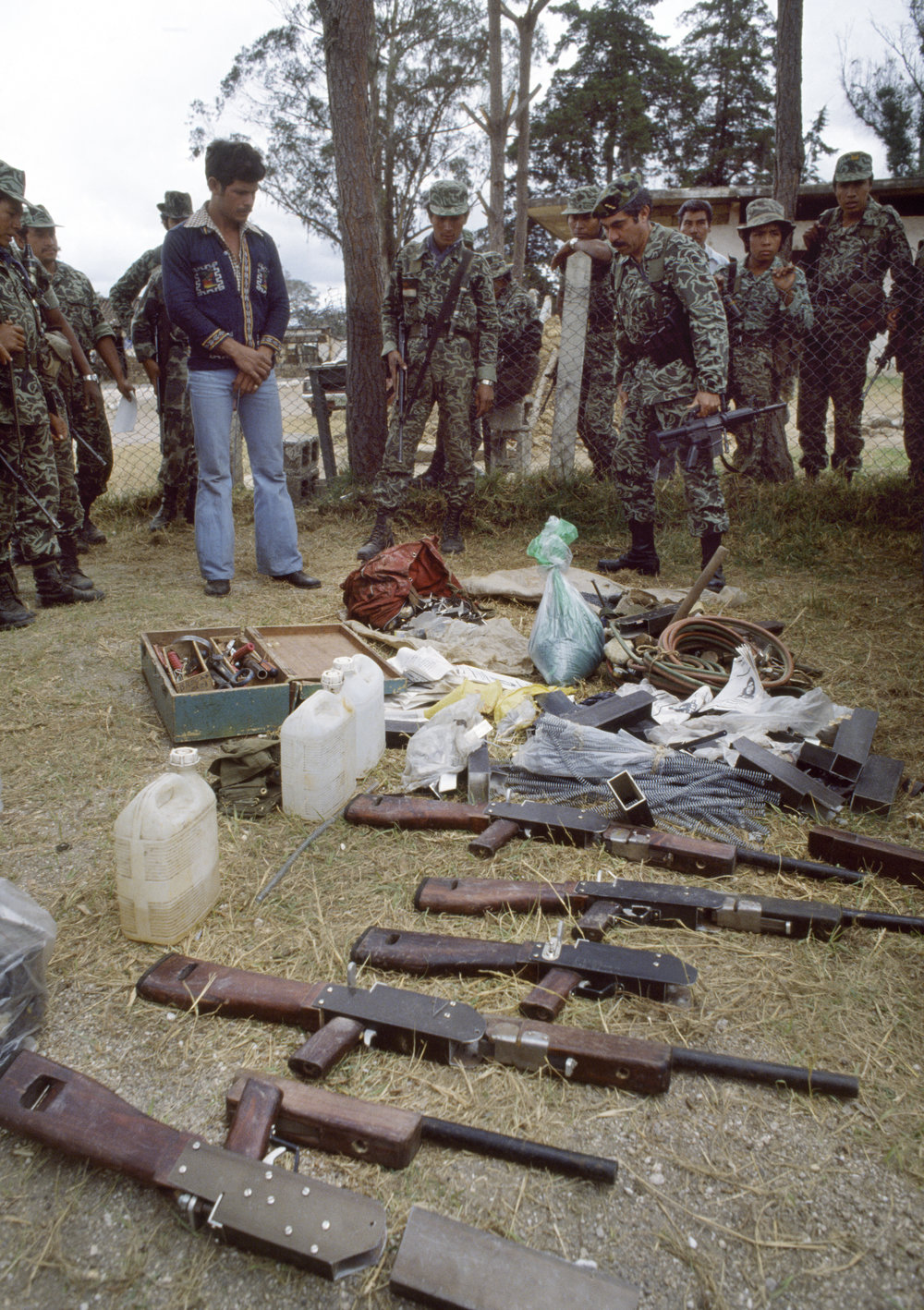 Guatemalan army Colonel Lima Estrada looks over captured weapons and explosives found in a Guerrilla Army of the Poor, EGP, safe house outside of Santa Cruz del Quiché, Guatemala on February 1, 1982. Col. Lima Estrada was the commander of the El Quiché army garrison.