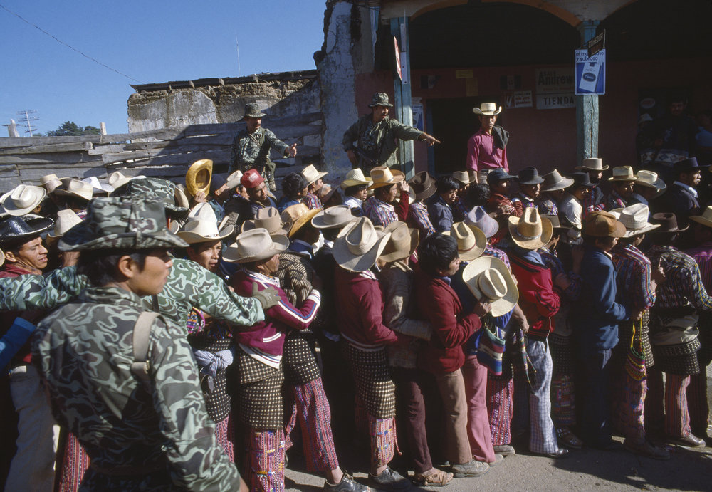 Guatemalan army soldiers oversee men lining up to vote in the presidential election in Sololá, Guatemala on March 7, 1982. The presidential election was won by retired General Ángel Ánibal Guevara but Guevara never took office following a March 23, 1982 coup d'état by General Ríos Montt.