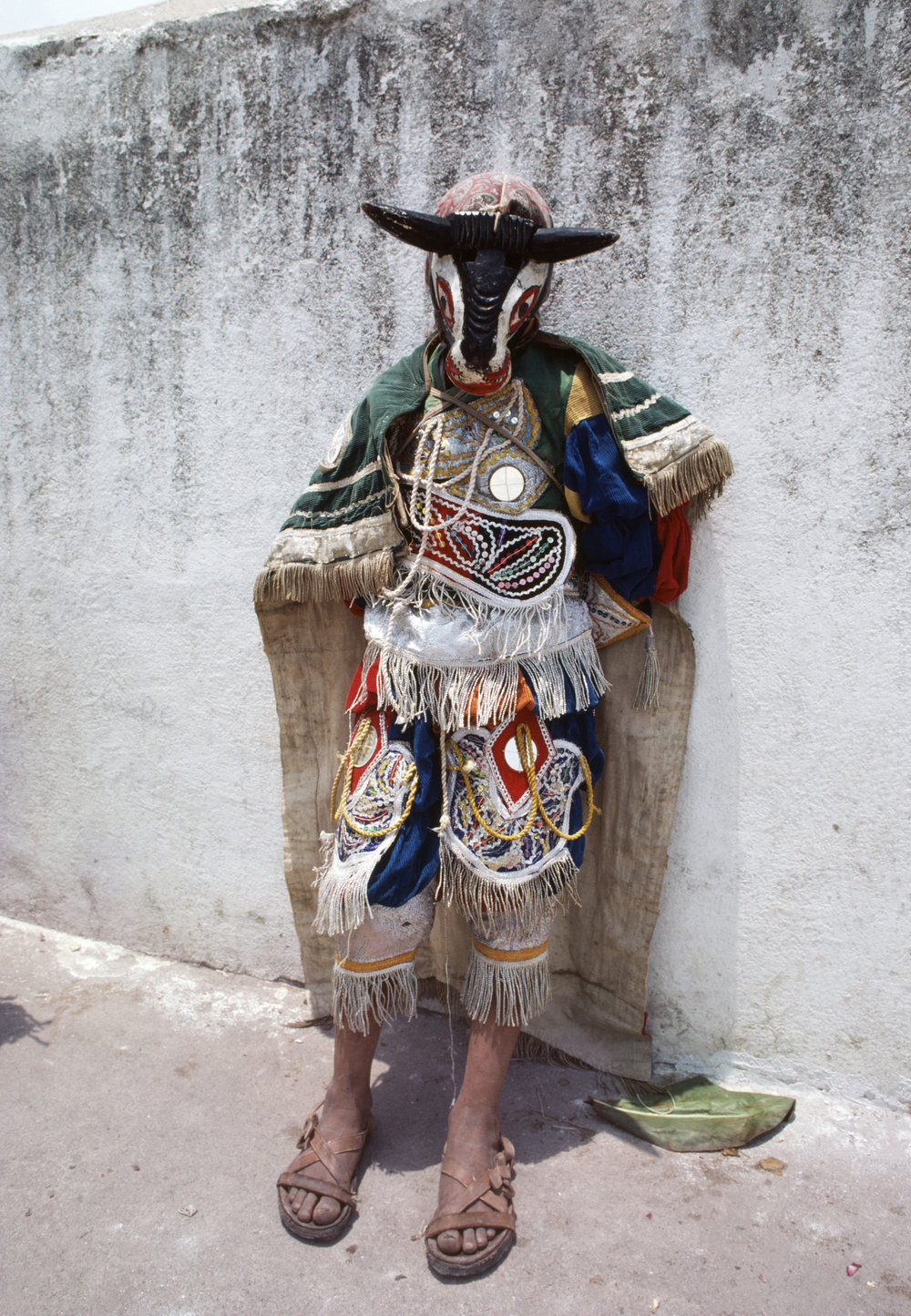 A Guatemalan man with a facemask of a bull stands against a wall during a festival near the Roman Catholic church of Santo Tomás in Chichicastenango, Guatemala May 1, 1982.
