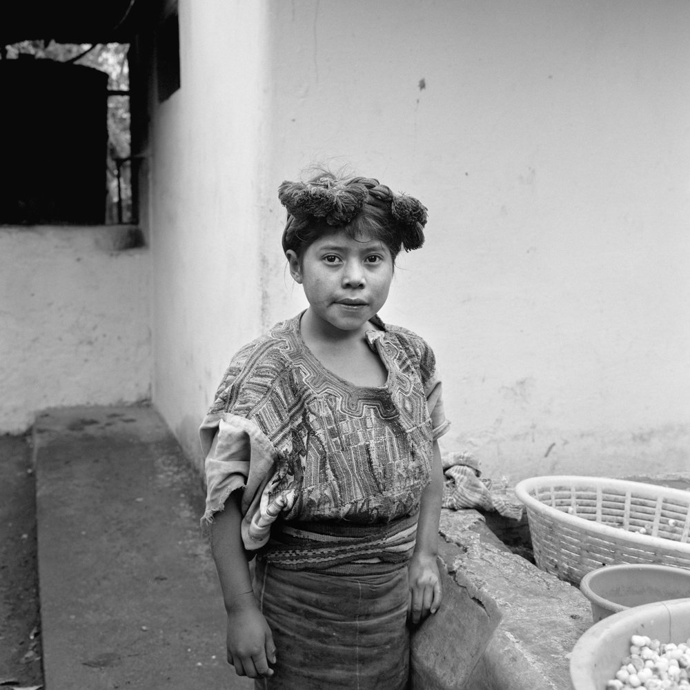 A young Ixil Maya woman, Juana Marcos Ramirez, wears a traditional Ixil head dress and huipil as she works in an open air kitchen in Nebaj, Guatemala, January 1, 1984.