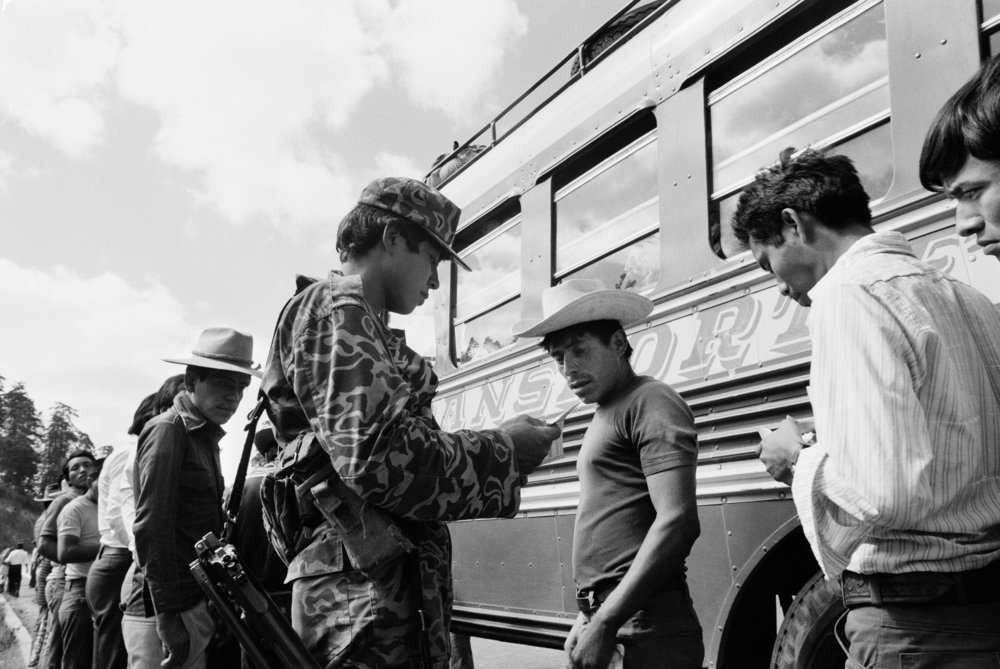 Army soldiers check identity cards of bus passengers along the Pan American Highway to Chichicastenango, Guatemala, March 1, 1982.