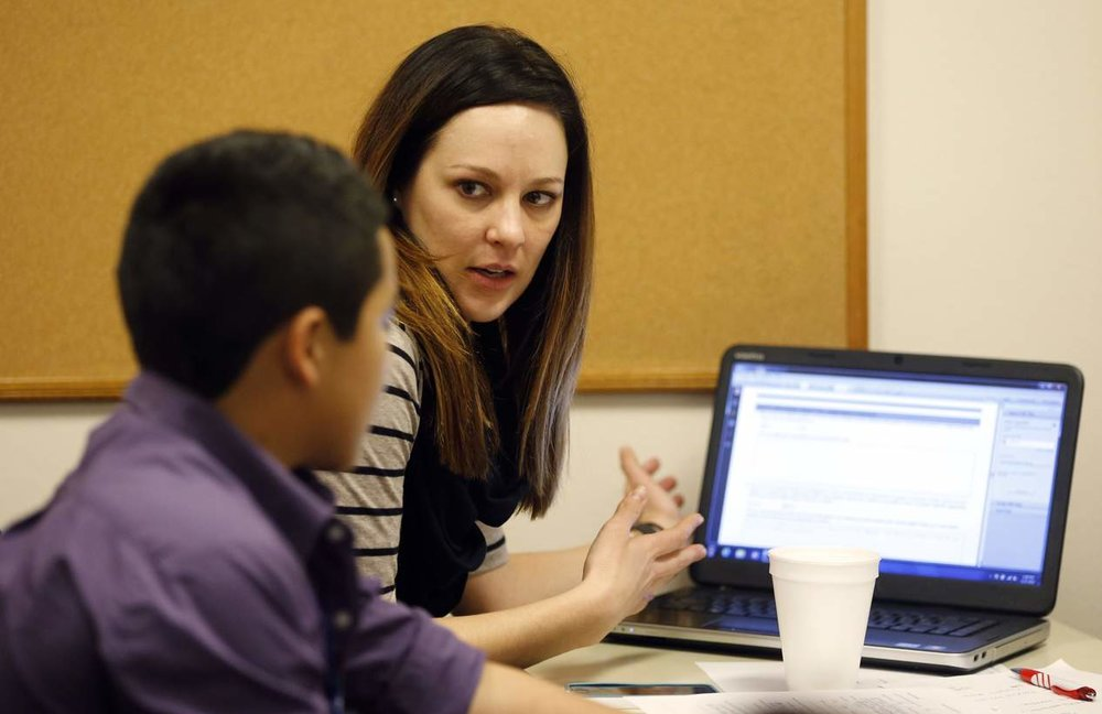 Volunteer Rachel Kingrey of Dallas helps a juvenile fill out an application during an asylum workshop at Catholic Charities in Dallas. (Vernon Bryant/The Dallas Morning News Photographer)